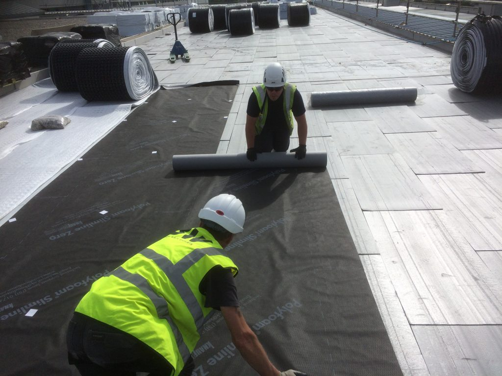 Green roof system drainage geosynthetics being installed